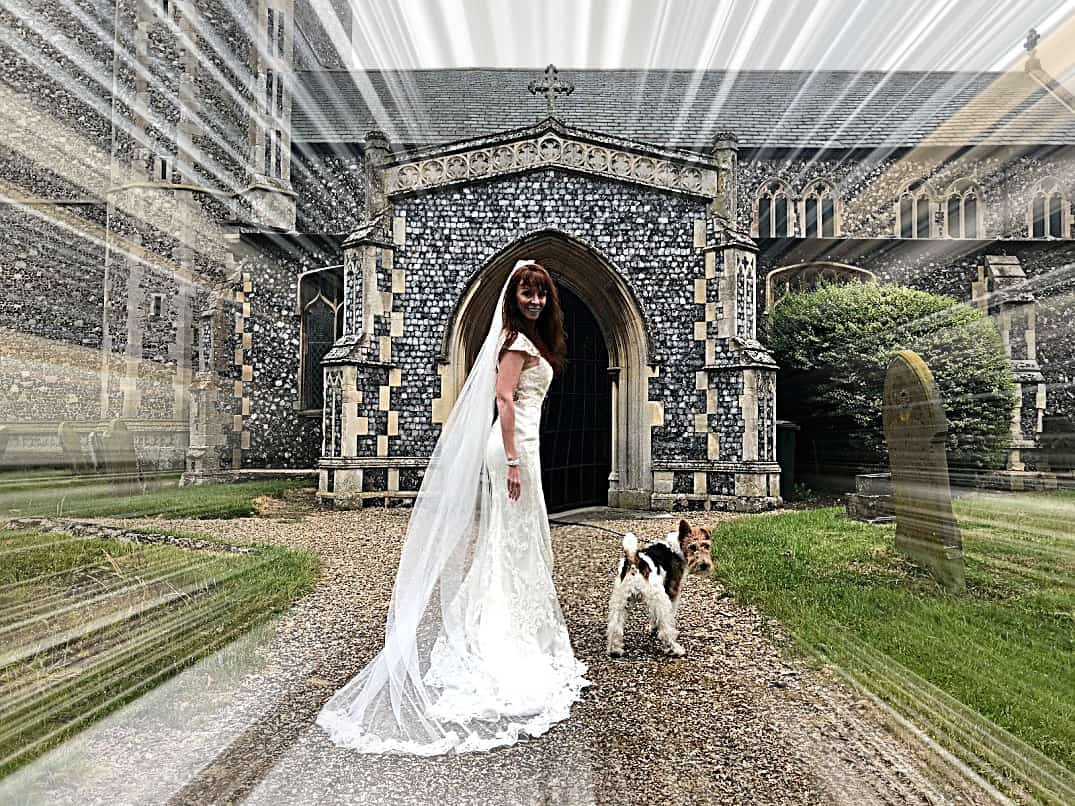 Tegan Marshall in the wandering wedding dress in England along with Pippin the fox terrier