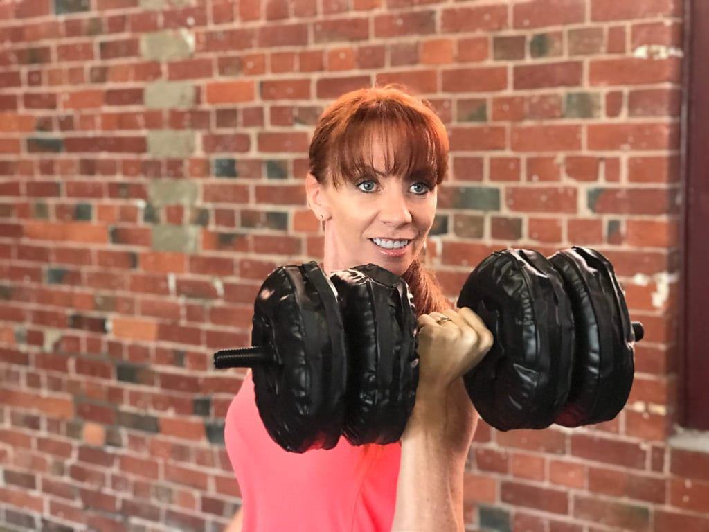 Tegan Doing Bicep Curl Exercise While Travelling Around The World With Water Weight Dumbells