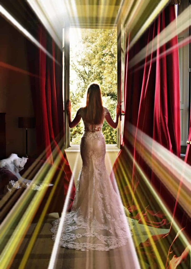 Tegan Marshall in the Wandering Wedding Dress in a window at Karma Tuscany