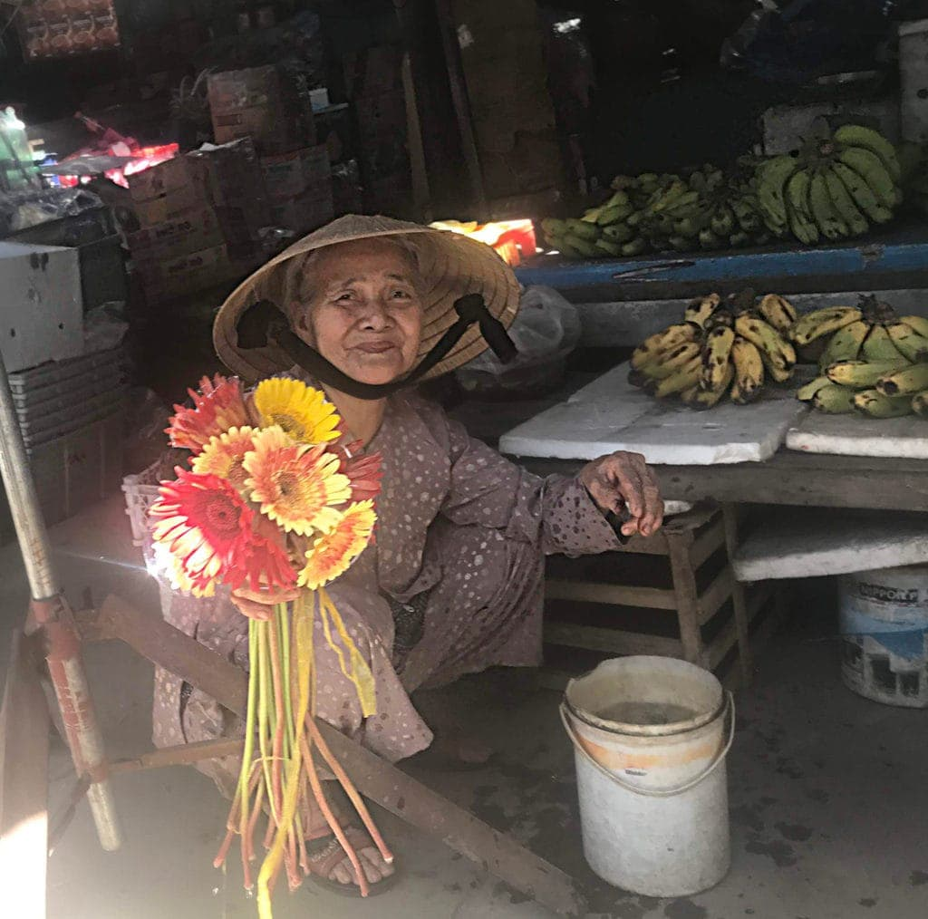Old Woman Offering Flowers For Sale At Local Markets For Courage To Travel Scaled 1