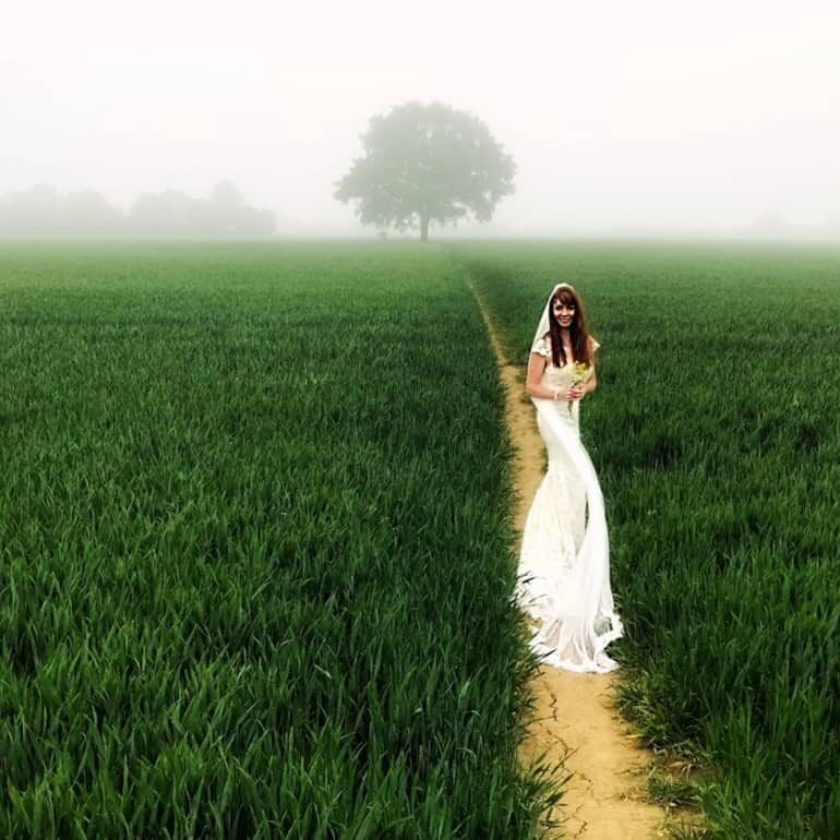 Image of Tegan Marshall in wedding dress in the fields of England